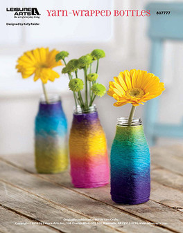 Craft a quick and colorful centerpiece to display using just yarn, bottles, and your creativity. Designed by Kelly Reider.