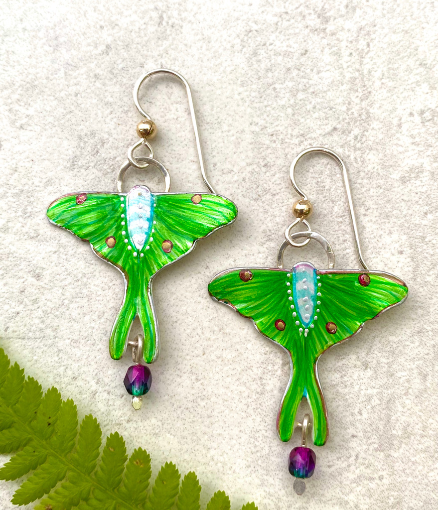 """What's not to love in a luna moth? They are one of nature's most magnificent creatures. These Luna Moth Earrings are a tribute to the real thing. They are handcrafted from jeweler's brass and Sterling silver, and carefully handpainted. They measure 1 1/2"""" x 1 1/2"""", and are light as a luna wing."""