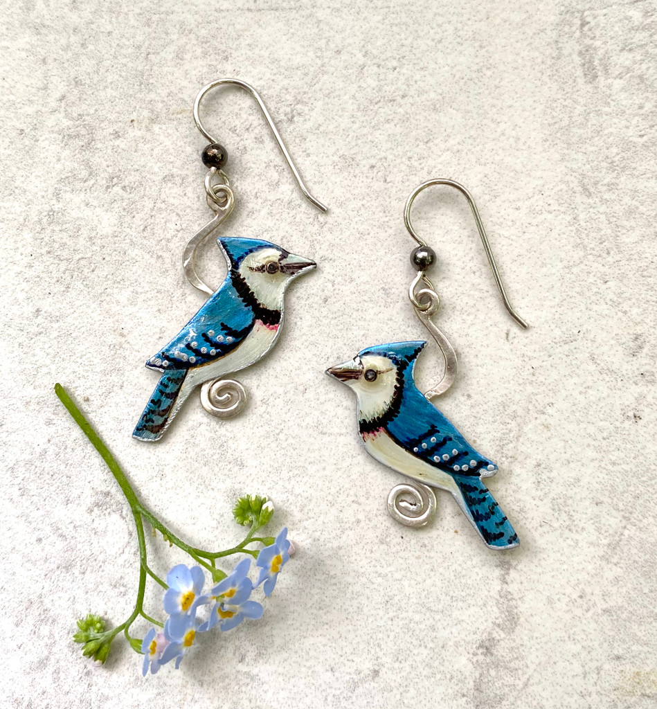 "These Blue Jay Earrings catch their namesakes in a rare still moment. They are handcrafted out of Sterling silver and jeweler's brass, and meticulously handpainted. They measure 1"" x 1 1/4"". They are light to wear and are a great gift for a friend or for you!"