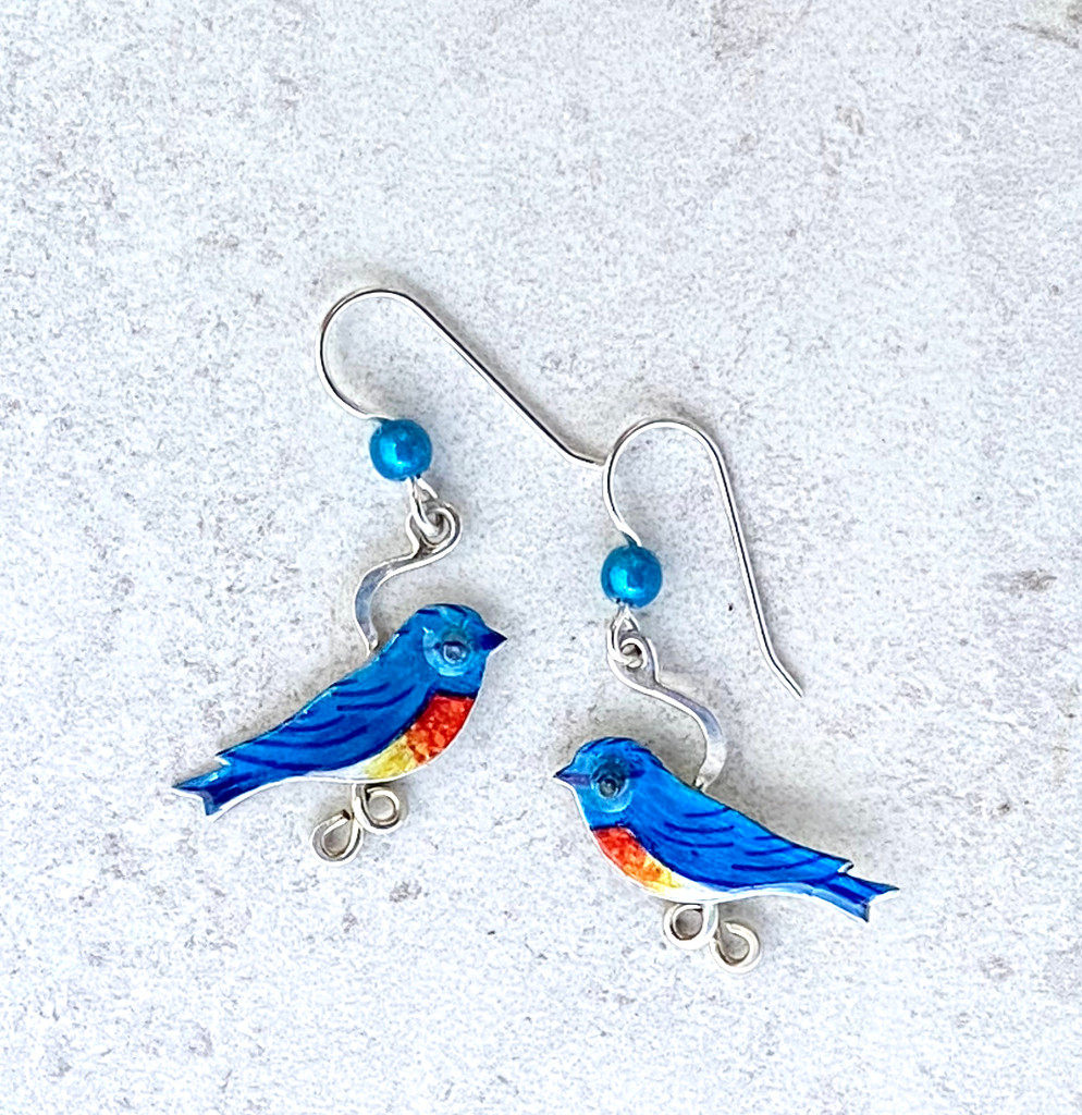 "The sight of a bluebird is always a treat, and these Bluebird Earrings are a reminder of that. They are handcrafted from Sterling silver and jeweler's brass, and carefully handpainted. They measure 7/8"" x 1"" and are as light as a feather."