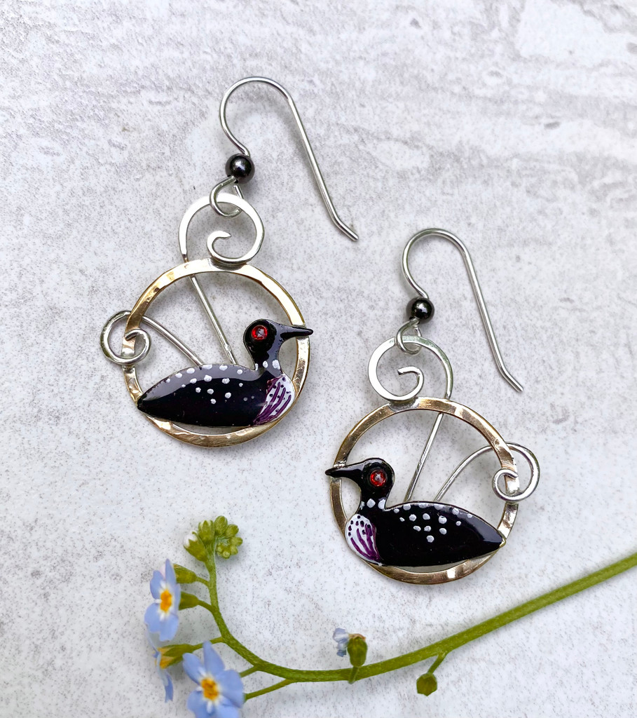 """The sight and sound of a loon is always special, and these earrings are a reminder of that. They are handcrafted from jeweler's brass and Sterling silver, and carefully handpainted. They measure 7/8"""" x 1"""", and are light as a feather to wear."""
