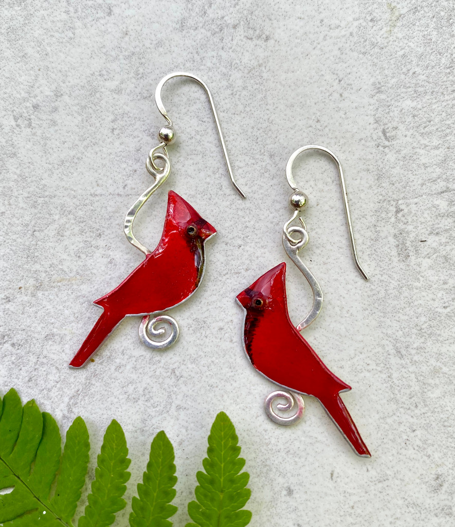 "You can't miss the flash of a cardinal, and these Cardinal Earrings are a reminder of what a thrill it is to see one. They are handcrafted from Sterling silver and jeweler's brass, and then carefully hand-painted. They measure 7/8"" x 1 1/8"", and are light as a feather."