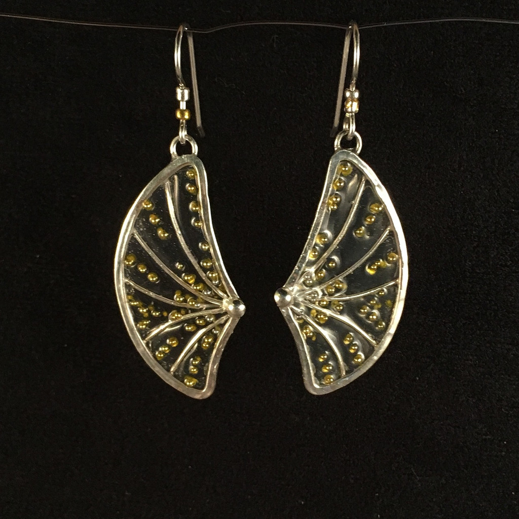 "What's not to love about earrings that provide lift to the day? These Golden Wing Earrings are carefully handcrafted out of Sterling wire which is has three layers of transparent jeweler's resin applied, embellished with gold ink and decorations. The result is striking and uplifting earrings that dance lightly when worn. They measure 1.5"" tall x .75"" wide not including the earring wires. They are lovely to wear and light as feathers."