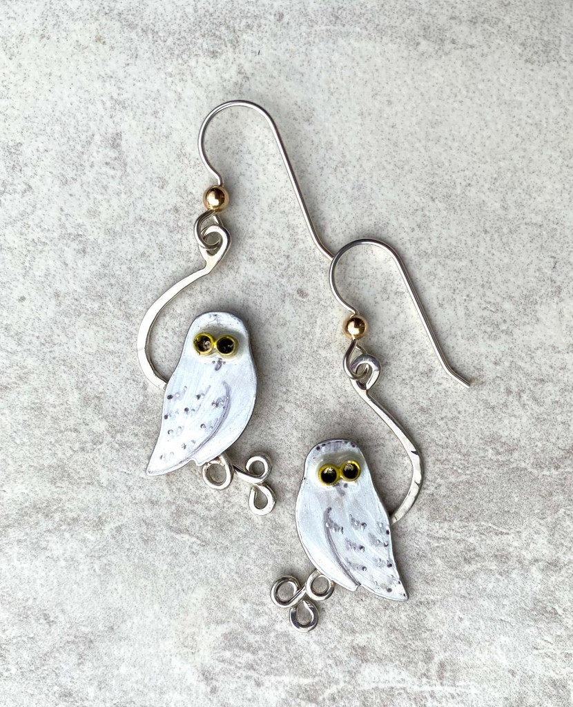 "Snowy owls are amazing! As an arctic bird of prey (and an avid lemming-eater), they sometimes migrate south in the winter, and are always a delight to see. As a result of long arctic winter days, they are diurnal, which sets them apart from most owls. These earrings pay homage to snowy owls. They are handcrafted from Sterling and jeweler's brass, and carefully painted and resined for durability. They measure 5/8"" wide, by 1 1/4"" tall, not including the earring wires. They are light and fun to wear and to give."