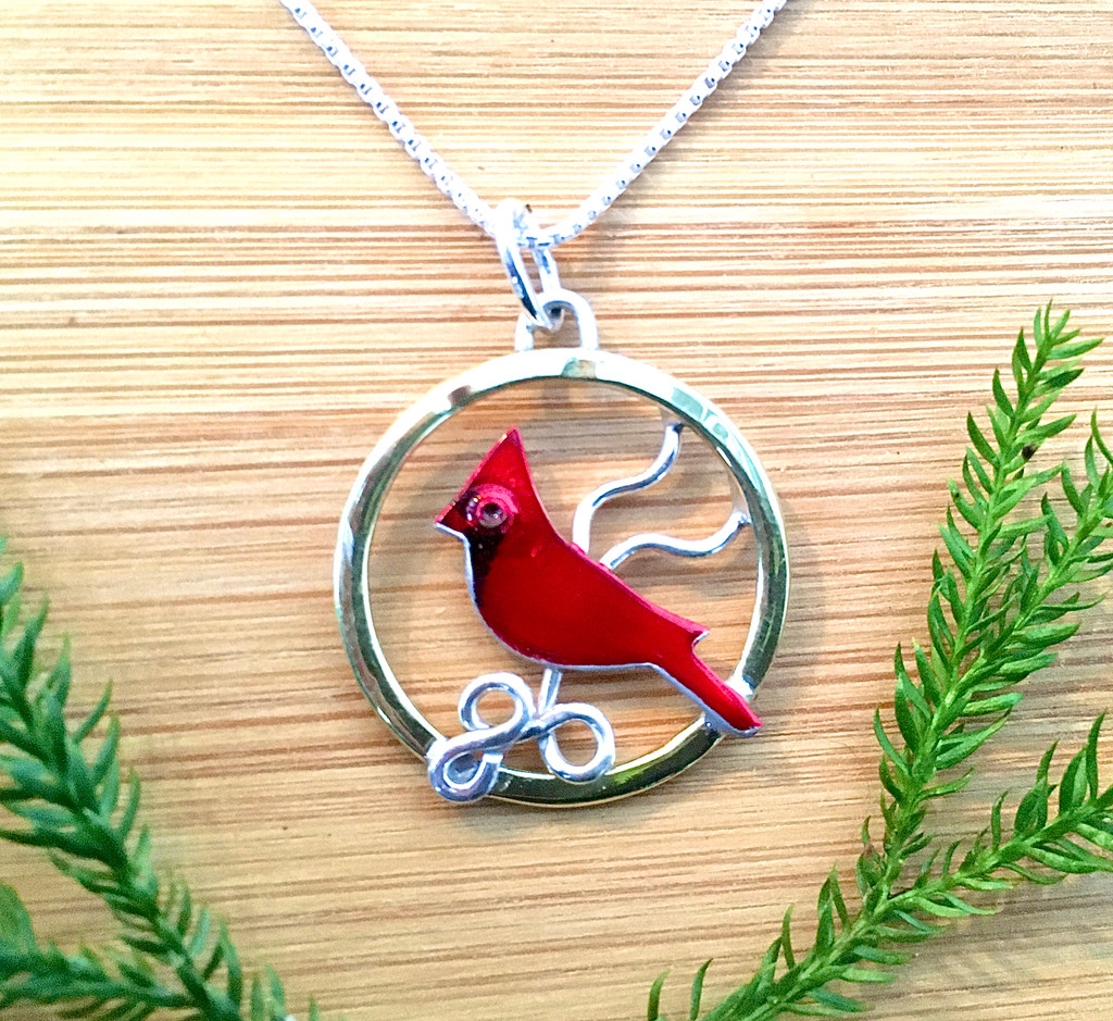 """You can't miss the flash of a cardinal and this Cardinal Necklace is a reminder of what a thrill it is to see one. It is handcrafted from Sterling silver and lacquered jeweler's brass and then meticulously hand-painted and protected with four clear coats, the final one being resin for depth of color and durability. The pendant measures 1"""" wide, and hangs from an 18"""" Sterling chain. It is the perfect gift for a friend or for yourself."""