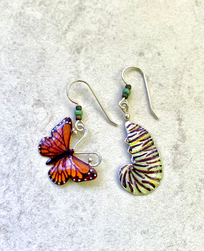 """One of the seven natural wonders of the world is the monarch butterfly migration. Both the individual monarch butterfly and its caterpillar stage are critical components of this miracle on earth. These earrings pay homage to both phases of the monarch's existence. I make them both out of jeweler's brass and Sterling and carefully hand-color each one, finishing them with jeweler's resin for depth and durability. They measure 7/8"""" wide x 1"""" tall, not including the earring wires. They are light and fun to give and to wear."""