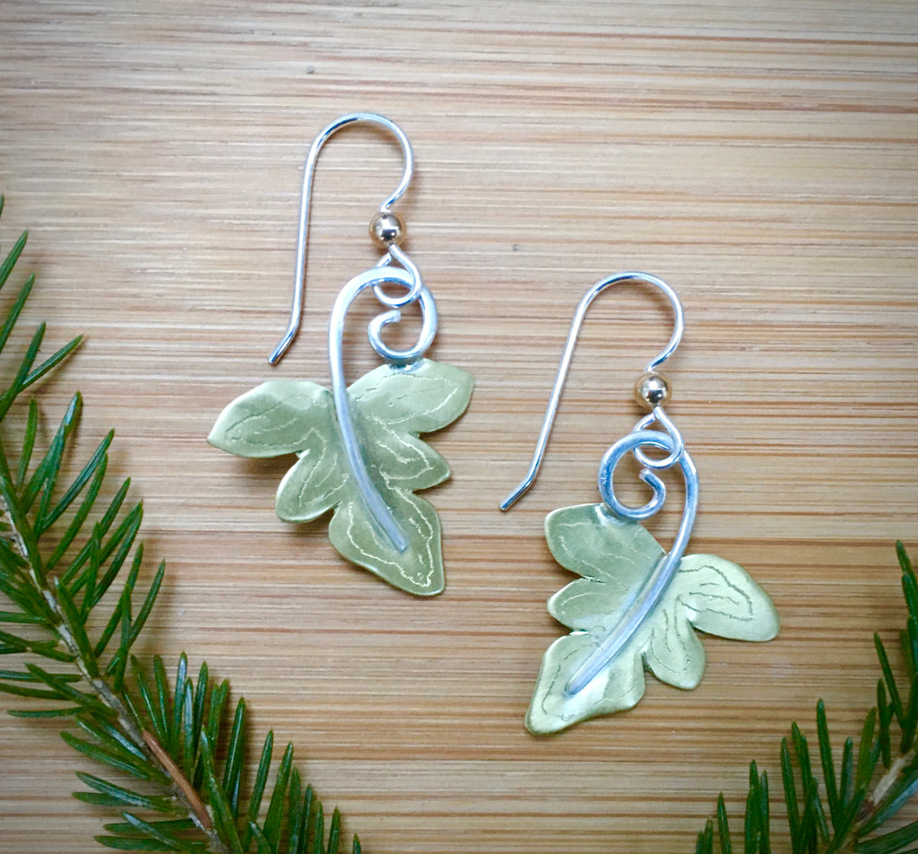 "Sensitive Fern Earrings, (Onoclea sensibilis), are inspired by the real thing. They are found in forests in Eastern North America, and are called this because the are sensitive to frost. These earrings are a tribute to the beauty of the ferns, and to the forests where they are found. They are handcrafted out of Sterling and jeweler's brass, and have a soft matte finish. They are lacquered to as to require minimal care. They measure 7/8"" wide x 1"" tall, not counting their Sterling earring wires."