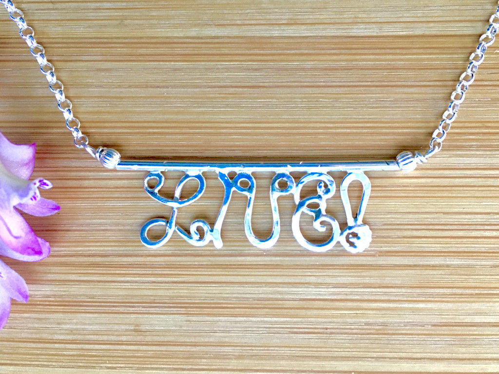 "What better message to embrace these days than to LIVE!? This necklace serves as a reminder of the importance of these four little letters. I make it out of Sterling silver wire. The focal point is 1 1/2"" wide by 1/2"" tall and the necklace is 20"" long in total. It's a great piece to wear and to give."