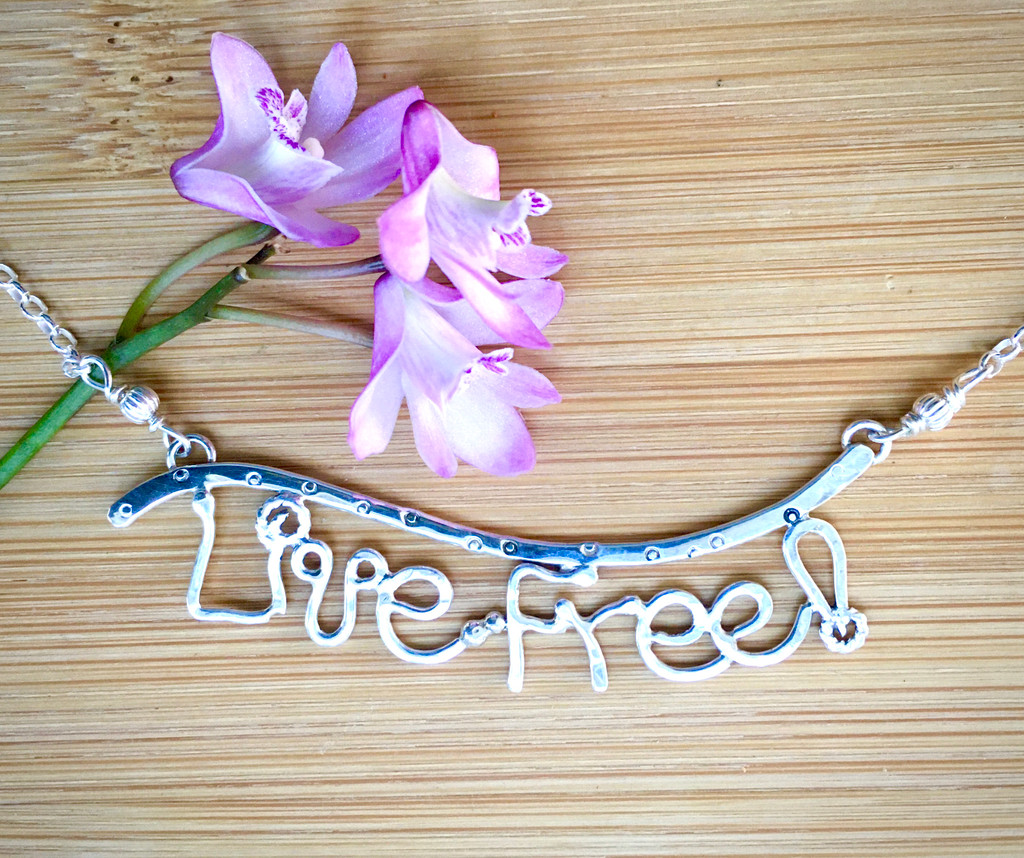 """These days of shifting tides and uncertainty present an opportunity to remember NH's motto and to Live Free!, a phrase that easily precedes """"and thrive"""". What better way to embrace this important message than to wear it. And what better form to wear it in than a handcrafted Sterling necklace. I freehand form each of the letters out of Sterling silver wire, and solder them. The letter focal point is 2 1/2"""" wide by 1/2"""" tall and the necklace is 20"""" long.It is the perfect piece to give or to wear."""