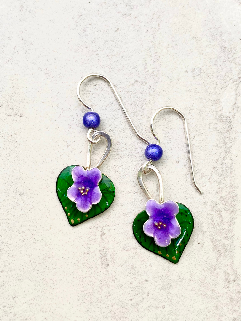"Everyone loves violets and these earrings are a reminder of this. They are carefully handcrafted out of Sterling and jeweler's brass and meticulously hand-colored. They measure 3/4"" tall by 1/2"" wide, not including the Sterling earring wires. They are light to wear, and would be the perfect gift for a friend or you!"