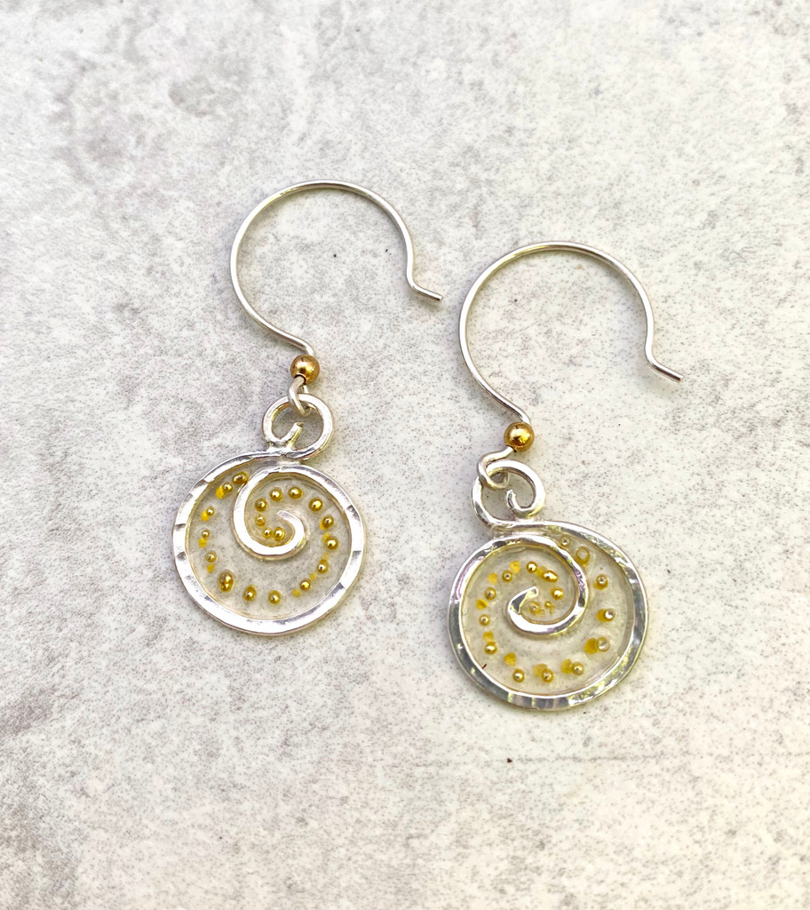 """We can all use a lift from time to time, and these Lighter Than Air Earrings provide just that; a touch of the ethereal. They are hand crafted from Sterling silver and have translucency that supports golden accents. They literally float when worn and add a bit of subtle sparkle. They measure 5/8"""" wide by 3/4"""" tall, not including the Sterling earring wires. They are light and comfortable to wear and are the perfect gift for a friend or for you!"""