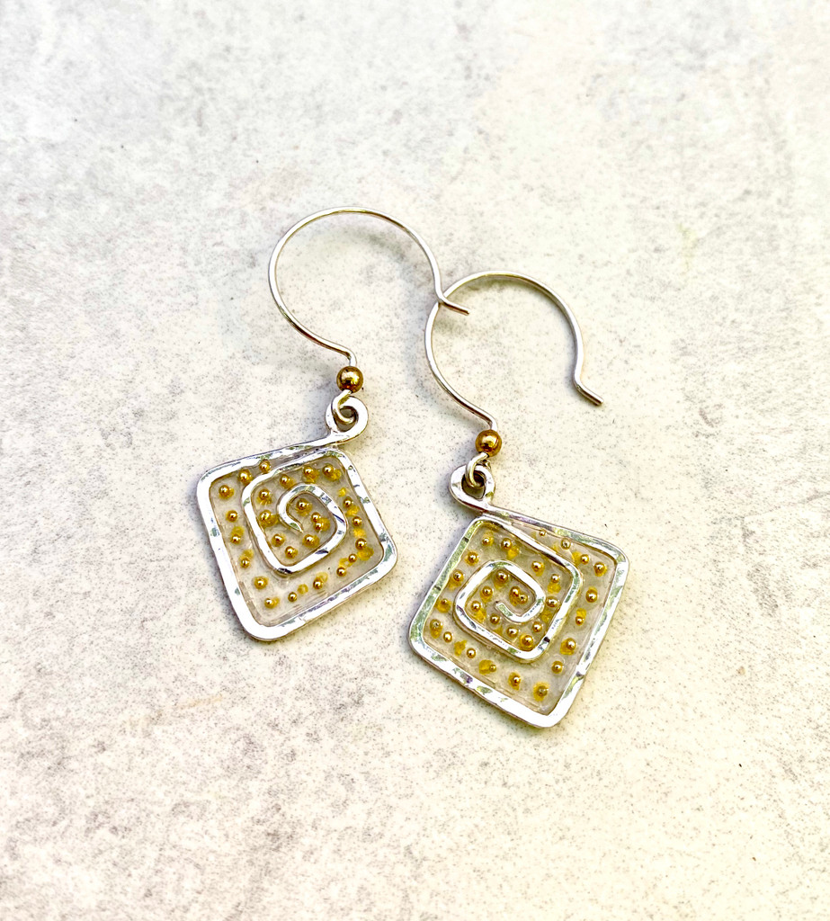 """We can all use a lift from time to time, and these Lighter Than Air Earrings provide just that; a touch of the ethereal. The square spirals suggest that square corners are but a myth, which is often the case. Life does not come in a clean package, and it certainly fit back into one as it expands. And why would we want it to? These earrings are a reminder of that grand fact. They measure 3/4"""" wide by 1"""" tall, not including the Sterling earring wires. They are light and fun to wear and make the perfect gift for a friend or yourself!"""