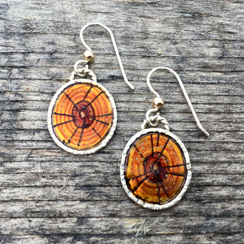 """Tree rings give a lovely history of the life of a tree, each ring representing a year of growth, so the older the tree, the more interesting the tree rings. Tree ring earrings are a reminder of this, as well as a tribute the the trees around us. They measure 4/5"""" tall x 5/8"""" wide not counting the earring wires. They are handmade out of sterling silver and lacquered brass that I have carefully handpainted and sealed with a durable layer of resin."""