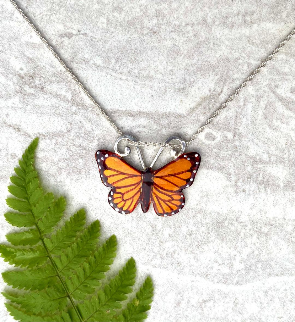 "Monarchs and their migration are yet another marvel of the natural world. This Monarch Butterfly Necklace is a tribute to their beauty and fortitude. It is handcrafted from jeweler's brass and Sterling silver, and then carefully handpainted, and finished with a coat of protective resin. The butterfly measures 1"" wide by 3/4"" tall and is strung on a 16"" chain. It would also work on an 18"" chain. If you would prefer the longer one, let me know in the notes."