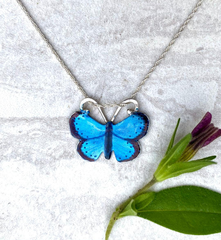 """The karner blue butterfly is endangered due to the loss of its foodsource, the wild lupine, or lupinus perennis. Due to the efforts of school children replanting this native wildflower, the karner blue is making a come-back. These Karner Blue Butterfly Necklace pays homage to this special butterfly, and to the efforts of those children. The butterfly is handcrafted from jeweler's brass and Sterling silver, and carefully hand-painted, then sealed with a protective coat of resin. It measures 7/8"""" by 7/8"""" and is strung on a 16"""" Sterling chain. It would also work on an 18"""" chain. Let me know in the notes if you would prefer the longer length."""