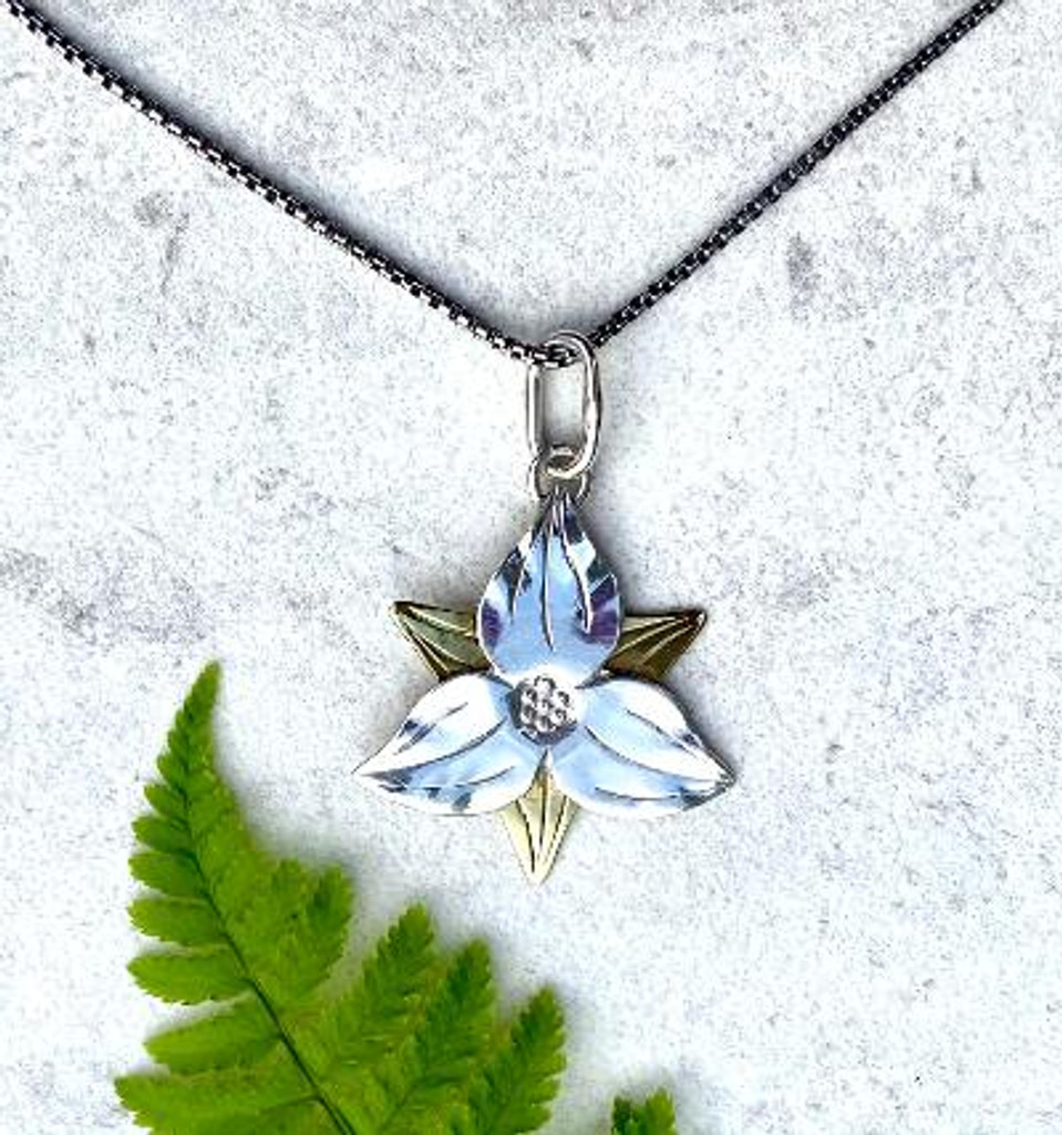 """Who doesn't love trilliums? This necklace is a tribute to a favorite wild flower. It is carefully handcrafted out of Sterling silver and lacquered jeweler's brass, and measures 1"""" by 1"""". It hangs on an 18"""" Sterling chain. It is the perfect gift for a friend or for you!"""