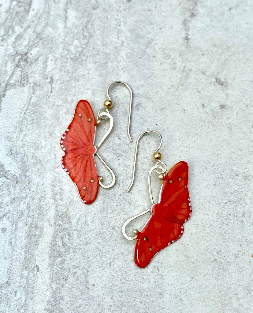 "The Julia Butterfly, Dryas iulia, is a brush-footed butterfly. Its range is from Brazil to the southern US. It is often seen in butterfly houses, and perches on people sometimes. It is a lovely orange butterfly with color variation between individuals. These earrings are a tribute to this butterfly. They are fabricated out of Sterling and jeweler's brass, and carefully handpainted and then sealed with a coat of protective resin. While hanging, they measure 3/4"" wide by 1 1/4"" long, not including the Sterling earring wires. They move gently while worn and are as light as a butterfly."