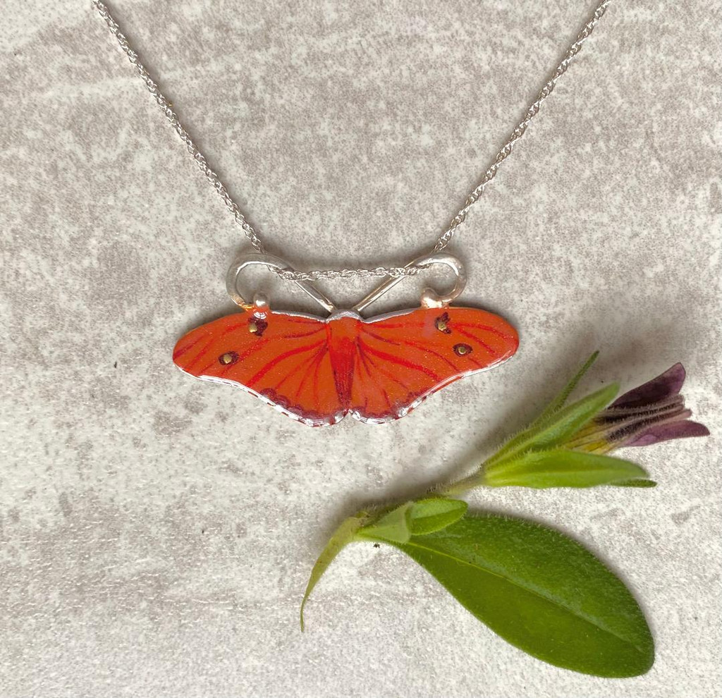 "The Julia Butterfly, Dryas iulia, is a brush-footed butterfly. Its range is from Brazil to the southern US. It is often seen in butterfly houses, and perches on people sometimes. It is a lovely orange butterfly with color variation between individuals. This necklace is a tribute to this butterfly. It is fabricated out of Sterling and jeweler's brass, and carefully handpainted and then sealed with a coat of protective resin. It measures 1 3/8"" by 5/8"" tall and is suspended from a 16"" Sterling chain, although it would also work on an 18"" chain. If you would prefer the 18"", please let me know in notes."