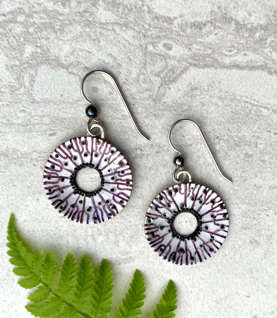 """Spore printing is one factor in identifying a mushroom. Caps are laid on white and black paper in order to see what color spores drop. The resulting pattern is really interesting, a star burst of sorts. These Black Spore Print Earrings are inspired by the real thing. They are handmade out of Sterling silver and jeweler's brass, and carefully handpainted, and then sealed with a protective coat of resin. They are studded with little silver """"spores"""" which give them sparkle and texture. They measure 7/8"""" in diameter, not including the Sterling earring wires."""