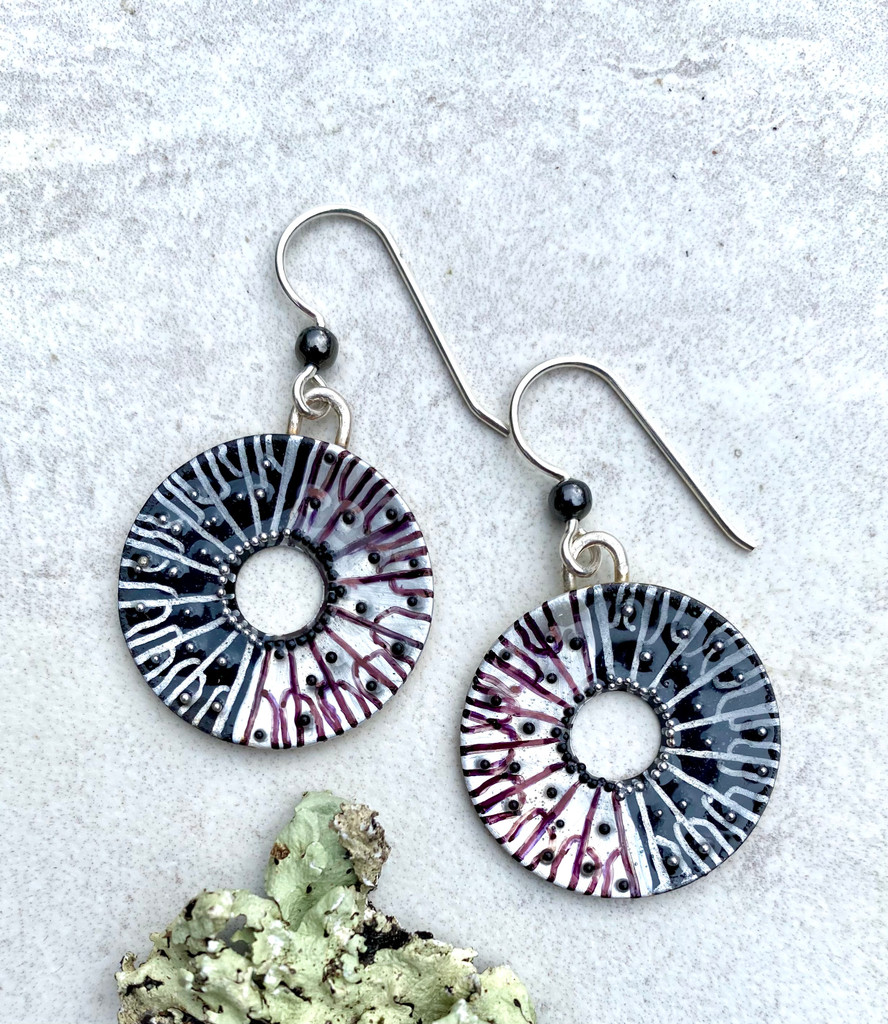 "Spore printing is one factor in identifying a mushroom. Caps are laid on white and black paper in order to see what color spores drop. The resulting pattern is really interesting, a star burst of sorts. These Black and White Spore Print Earrings are inspired by the real thing. They are handmade out of Sterling silver and jeweler's brass, and carefully handpainted, and then sealed with a protective coat of resin. They are studded with little black and silver ""spores"" which give them sparkle and texture. They measure 7/8"" in diameter, not including the Sterling earring wires."