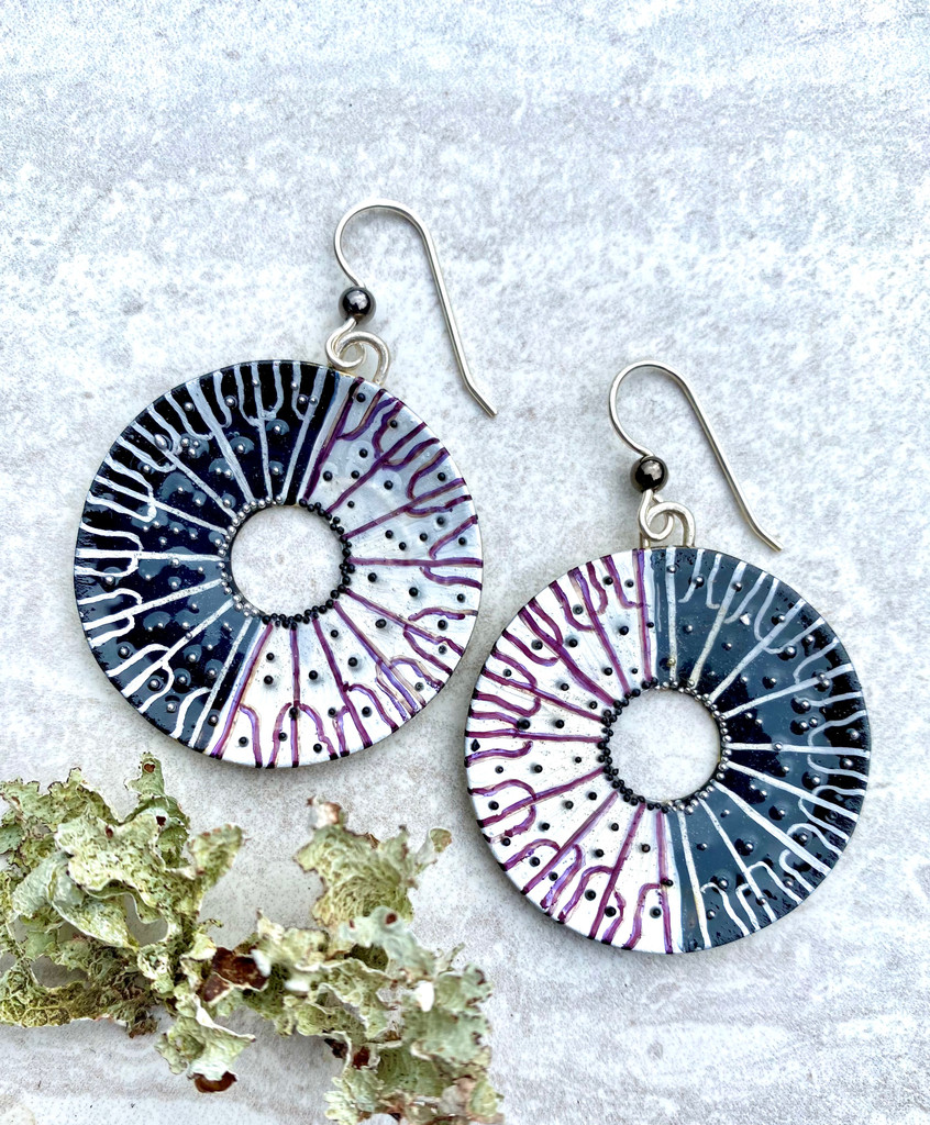 """Spore-printing is one factor in identifying a mushroom. Caps are laid on white and black paper in order to see what color spores drop. The resulting pattern is really interesting, a star burst of sorts. These Black and White Spore Print Earrings are inspired by the real thing. They are handmade out of Sterling silver and jeweler's brass, and carefully hand-painted, and then sealed with a protective coat of resin. They are studded with little black and silver """"spores"""" which give them sparkle and texture. They measure 1 3/8"""" in diameter, not including the Sterling earring wires."""