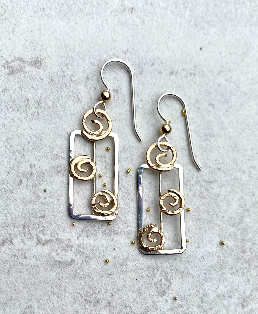 """In these days of transitioning to best living practices for the conservation and the preservation of our planet, celebrating the vehicles that we are increasingly using for this goal seems both appropriate and even essential. It is in this spirit that Solar Panel Earrings were conceived. They are fabricated out of Sterling """"grids"""" and embellished with 14k gold-filled swirls of energy-giving sunshine. They measure 1/2"""" wide by 1 1/8"""" tall, not including the Sterling earring wires. They are a lovely symbol of a movement that will ultimately save our planet."""
