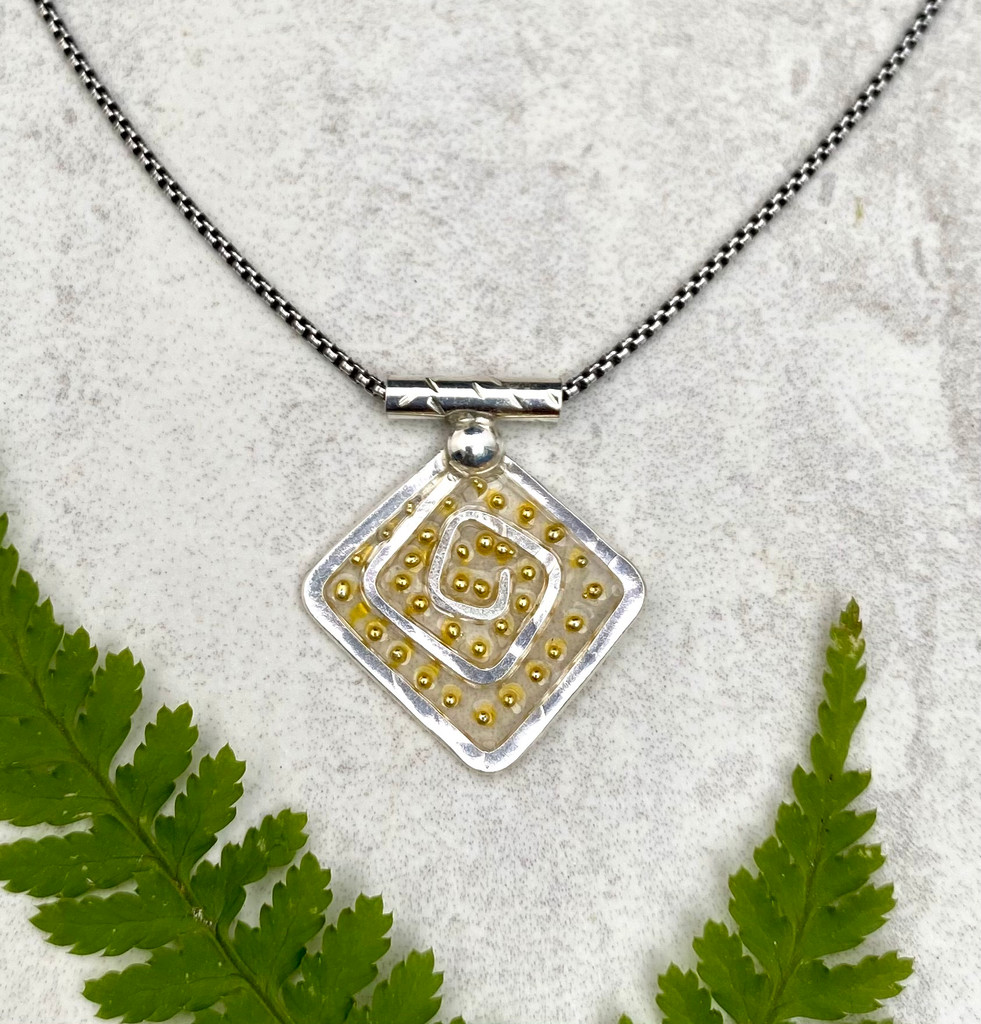 """For those of us who can use some levity these days, the Lighter Than Air Spiral Circle Necklace enters stage right. So why lighter than air? The necklace features a Sterling spiral, which is in itself, a powerful image suggesting a connection to infinity, a potentially ethereal  concept. It also features translucency...pretty airy...and is embellished with little golden dots which suggest, what else(?)-- light. So all in all, it says light and lightness. The spiral measures 3/4"""" wide by 7/8"""" tall. It is suspended on a 20"""" Sterling chain."""