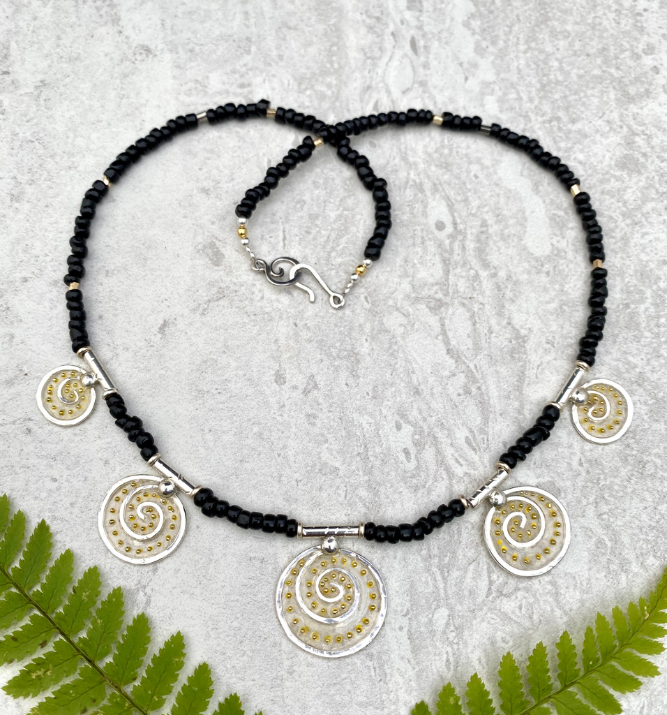 For those of us who can use some lovely levity these days, the Lighter Than Air Dancing Circle Necklace enters, stage right. It is comprised of five handmade Sterling circular spirals of graduated sizes, strung with black and gold glass beads, and finished with a handmade clasp, featuring, what else....a little spiral. So why lighter than air? The spiral itself is a powerful image that suggests a connection to infinity, a potentially light concept. These spirals feature translucency....pretty airy....and are embellished with little golden dots, which suggest, what else(?)--light! So all in all, the necklace is a beautiful way add a bit of bling and lighten the mood at the same time. It measures an ample 18 inches.