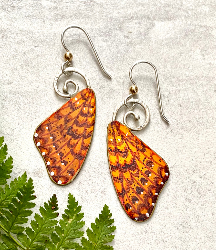 """The White Mountain Fritillary is a very special species of butterfly. Fritillaries are found around the world, but this one is only lives above 4000 feet and in the Presidential Range of the White Mountains of NH. Because of the short season there, its life cycle spans two years. These earrings pay tribute to the butterfly. I make them out of Sterling and jeweler's brass, and apply a variety of media to hand-color them, including a final coat of jewelry resin to protect them. They measure 1 1/2"""" tall by 3/4"""" wide, not including their Sterling earring wires. They are light to wear and make great gifts!"""