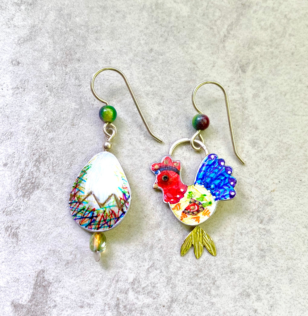 """The quintessential question manifested in jewelry. These chicken and egg earrings are colorful and fun to wear. They are handcrafted out of Sterling Silver and Jeweler's Brass, and then handpainted and finished with finished with a protective coat of resin. They come on Sterling pierced earring wires, although non-pierced clips can be substituted by request. Their size is 3/4"""" x 1 1/4""""."""