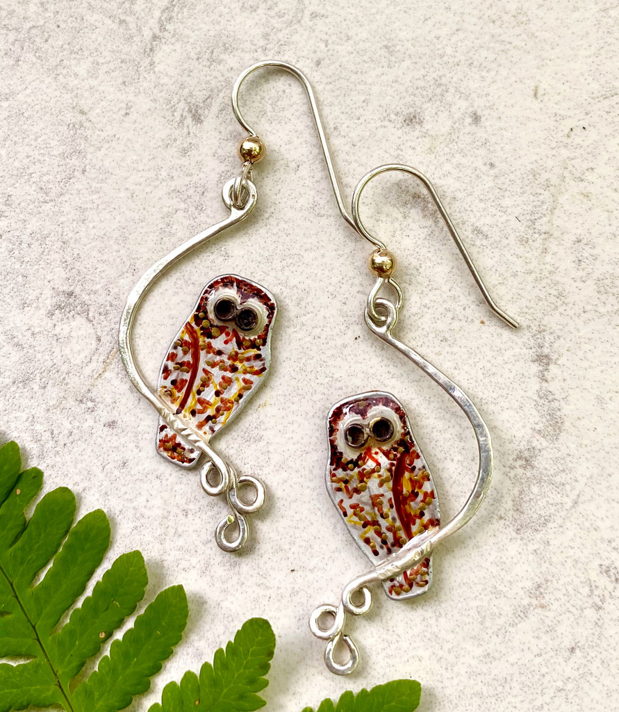 """The sight of an owl is always a special event. These Barred Owl Earrings serve as a reminder of this. They are handcrafted out of Sterling Silver and Jeweler's brass, and meticulously handpainted and sealed with a protective coat of resin. The Sterling Silver wires are for pierced ears, but non-pierced clips may be substituted by request. Their size is 5/8"""" x 1 1/4"""". They are light as an owl's feather to wear."""