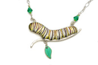"""Because our world can use all the monarchs it can get, the Monarch Caterpillar Necklace has arrived. The monarch butterfly population has dropped significantly over the last ten years, but this year was more promising than any of the last five. What happened to help to turn around this icon of the natural world? No one knows for sure, but awareness of the issue is no doubt key. And wearing monarch-themed apparel, either in butterfly or caterpillar form, helps to raise this awareness. And then there is the fact that both stages of this butterfly are beautiful and fun to wear. This necklace is 18"""" long. The caterpillar itself, along with its supportive stick, is 2.5"""" long 1.75 tall, including the dangling milkweed leaf. The chain is Sterling Silver, and the caterpillar is lacquered and painted brass, along with Sterling embellishments. I have carefully painted the caterpillar, and the protected it with various protective clear coats, topping it with a bullet-proof, shimmery resin coat. This necklace is the ultimate tribute to monarch butterflies."""