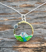 """John Muir's quote, """"The Mountains are calling and I must go"""", resonates with all of us, and this mountain  necklace will too. It is is a tribute to the beauty and sanctity of our earth's mountains. I have fabricated it out of brass and Sterling, and hand-colored it, protecting it with 3 clear-coats, the final one being a tough resin. Metal components are lacquered. It measures a generous 3/4"""" in diameter and is light to wear. It hangs from an 18"""" Sterling silver chain."""