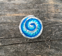 "Ocean waves and waterfalls emit feel-good negative ions. This tie tack/lapel style pin may not actually emit the ions (but who knows?), but it will promote feelings of hope and peace. It is handcrafted out of Sterling and three layers of jewelry resins. It measures 3/4"" wide."