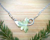 "This Small Sensitive Fern Necklace, (Onoclea sensibilis), is inspired by the real thing. Sensitive ferns are found in forests in Eastern North America, and are called this because the are sensitive to frost. These necklace is a tribute to the beauty of the ferns, and to the forests where they are found. It is handcrafted out of Sterling and jeweler's brass, and has a soft matte finish. It is lacquered to as to require minimal care. The fern measures 7/8"" wide x 1"" tall, and the Sterling chain is 18"", which makes the necklace 19"" with the fern."