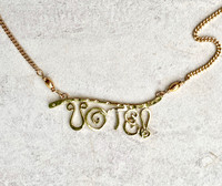 "The right to vote in a democracy is one that needs to be exercised for the system to work. This necklace pays homage to this right, and serves as both a statement and an important reminder. It is handcrafted out of jeweler's brass with a gold-plated chain. It measures 19"" with the chain, and is adjustable to 17"". The focal point is lacquered to prevent tarnish and measures 1 3/4"" wide by 5/8"" tall. It is an elegant piece to give or to wear."