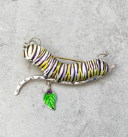 """The monarch caterpillar is always a welcome sight. The monarch migration is one of the many wonders of our world, and as such, each part of the monarch life cycle is a star in the natural world. This Monarch Caterpillar Pin is a tribute to this lovely creature. I make it out of Sterling silver and lacquered jeweler's brass, and carefully hand-paint it, sealing it with a protective coat of resin. It measures 2 1/2"""" wide by 1 3/4"""" tall, including the dangling milkweed leaf. It serves as a lovely reminder of the beauty and power of our natural environment."""