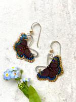 """The mourning cloak butterfly is special in that it hibernates, allowing it to emerge on those early warm spring days, and then go back into hiding when the temperature drops again. It is a butterfly with a rich appearance, a lovely chocolate brown with a silvery gold border lined with blue spots. These Mourning Cloak Butterfly Earrings pay tribute to this favorite butterfly. I fabricate them out of Sterling silver and jeweler's brass, and carefully hand-paint each one. They are sealed with a protective coat of resin. The measure almost 1"""" wide by 1"""" tall not including their Sterling earring wires. They are light as a butterfly's wing to wear, and make great gifts."""