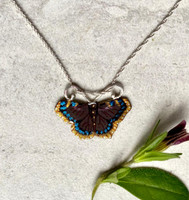 "The mourning cloak butterfly is special in that it hibernates, allowing it to emerge on those early warm spring days, and then go back into hiding when the temperature drops again. It is a butterfly with a rich appearance, a lovely chocolate brown with a silvery gold border lined with blue spots. This Mourning Cloak Necklace pays tribute to this favorite butterfly. It is fabricated out of Sterling silver and jeweler's brass, and carefully hand-paint and sealed a protective coat of resin. The butterfly measures 1"" wide by 3/4"" tall and is strung on a 16"" Sterling chain. It would also work on an 18"" chain, and if you would prefer that, let me know in the notes. The necklace is a tribute to a very special butterfly."