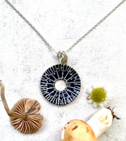 """Spore printing is one factor in identifying a mushroom. Caps are laid on white and black paper in order to see what color spores drop. The resulting pattern is fascinating, a star burst of sorts. This Black Spore Print Necklace is inspired by the real thing. It is handmade out of Sterling silver and jeweler's brass, and carefully hand-painted, and then sealed with a protective coat of resin. It is studded with little silver """"spores"""" which give it sparkle and texture. It measures 7/8"""" in diameter and is suspended on an 18"""" Sterling chain."""