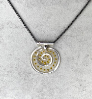 "For those of us who can use some levity these days, the Lighter Than Air Spiral Circle Necklace enters stage right. So why lighter than air? The necklace features a Sterling spiral, which is in itself, a powerful image suggesting a connection to infinity, a potentially light concept. It also features translucency...pretty airy...and is embellished with little golden dots which suggest, what else(?)-- light. So all in all, it says light and lightness. The spiral measures 3/4"" wide by 7/8"" tall. It is suspended on a 20"" Sterling chain."