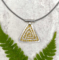 """For those of us who can use some levity these days, the Lighter Than Air Spiral Pyramid Necklace enters stage right. So why lighter than air? The necklace features a Sterling spiral, which is in itself, a powerful image suggesting a connection to infinity, a potentially ethereal concept. It also features translucency...pretty airy...and is embellished with little golden dots which suggest, what else(?)-- light. And then of course there is the pyramid shape, representing the rays of the sun. So all in all, it says light and lightness. The spiral measures 1"""" wide by 1"""" tall. It is suspended on a 20"""" Sterling chain."""
