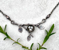 """It is always a thrill to encounter a bird's nest, and even more so when it is cradling eggs. This bird nest necklace is a testament to this. It is hand-fabricated out of Sterling silver and features fresh-water pearls. The focal point measures 1"""" tall by 2"""" wide and the total length with the oxidized Sterling chain is 19"""". It is a sweet necklace that resonates with those who thrive in the great outdoors, those who cherish what it means to be a parent, as well as all the bird-lovers amongst us.  Note re custom nests: I am happy to accommodate special requests re the number of eggs in the nest. It comes with 3 peal eggs, but if more or less are desired, within reason (not sure if 24 eggs would fit...) please let me know in the notes. I will confirm this via email.   """"You'll have a lot more respect for a bird after you try making a nest."""" ---Cynthia Lewis"""