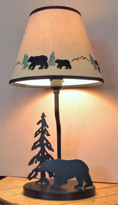 """Black metal lamp features a bear and a pine tree silhouette. Base is 8"""" across, lamp is 18"""" high. Tan shade has embroidered bears and pine trees. Shade is 10"""" diameter at bottom."""