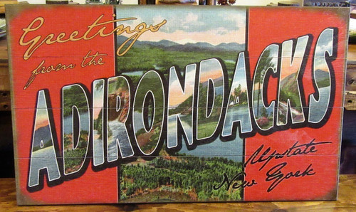 """Vintage style wooden sign says 'Greetings from the Adirondacks'. Bright images of the Adirondacks. Measures 30"""" x 18""""."""