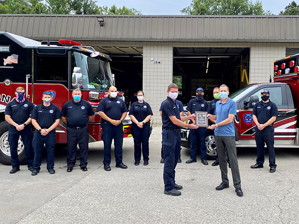 A group of firefighters present CEO Kevin Nolan with a plaque as a token of their appreciation for new freezers provided to their department through the GEA4Heroes program.