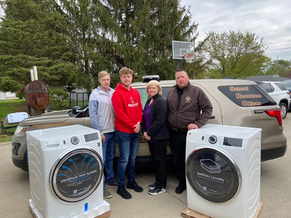 GEA4Heroes recipients Kevin and Mindy Brown of Hartford, Ind., take a photo with their sons and new washer and dryer.