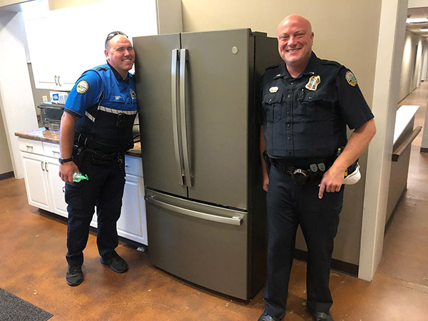 Two Chattanooga police officers smile next to their new GE refrigerator.