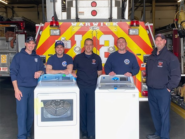 Five firefighters stand behind their new washer and dryer for a photo.