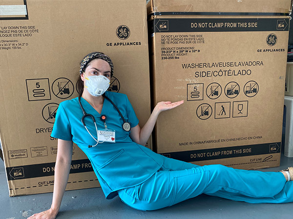 Nurse Victoria Gonzalez poses on the floor next to her new washer and dryer pair.